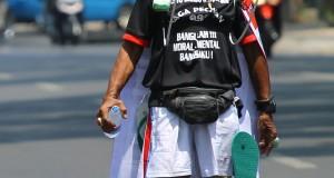 Kusno (66) pejalan kaki mundur dari Malang menuju Jakarta menggunakan kaca spion untuk melihat arah saat melintas di jalan semeru, Malang, Jawa Timur,