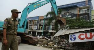 Anggota Satpol PP mengawal Alat berat membongkar bangunan liar semi permanen di sisi selatan Kalimalang, jalan KH.Noer Alie, Bekasi, Jawa Barat, Kamis (23/10),