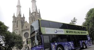 Bus tingkat wisata Ibukota melintas di depan Gereja Katedral Jakarta, Senin (6/10).