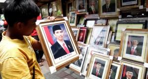 Pedagang membersihkan foto Presiden dan Wakil Presiden Joko Widodo - Jusuf Kalla di Pasar Baru, Jakarta,  Jumat (24/10).