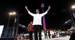 Presiden Ke-7 RI Joko Widodo memberikan salam tiga jari saat menghadiri puncak acara Syukuran Rakyat di Silang Monas, Jakarta, Senin (20/10)