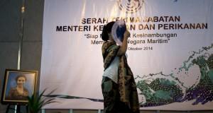 Menteri Kelautan dan Perikanan baru Susi Pudjiastuti menutup wajahnya dengan kipas muka usai serah terima jabatan menteri kelautan dan perikanan di Kantor Kementerian KKP, Jakarta, Rabu (29/10).