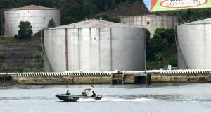 Perahu penumpang melintas di dekat Terminal Bahan Bakar Minyak (TBBM) milik Pertamina di Pulau Sambu, Batam, Selasa (21/10). Pulau Sambu yang berhadapan