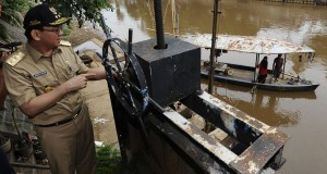 Plt Gubernur DKI Jakarta Basuki Tjahaja Purnama atau Ahok mencoba mengoperasikan kran pintu air ketika meninjau bantaran Kali Ciliwung di Kebon Baru, Tebet, Jakarta Selatan, Selasa (18/11).