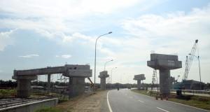 Sejumlah pekerja menyelesaikan pembangunan infrastruktur jalan tol di Kualanamu Deli Serdang, Sumut, Minggu (9/11). Pembangunan jalan tol