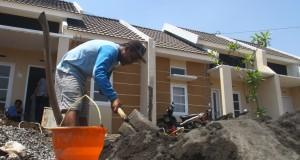 Seorang pekerja menyelesaikan pekerjaannya membangun rumah di kawasan perumahan milik Perum Perumnas, Sawojajar, Malang, Jawa Timur