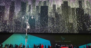 Pedestrians walk underneath a giant new advertising screen in Times Square, New York