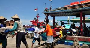 Sejumlah nelayan menurunkan hasil tangkapan ikan usai melaut di Pelabuhan Tegalsari,