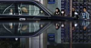People in front of an electronic board, showing various stock prices, are reflected in a polished stone surface outside a brokerage in Tokyo