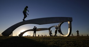 Youths climb on top of a sculpture in the form of a giant pair of spectacles on Cape Town's Sea Point Promenade