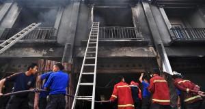 Petugas pemadam kebakaran berusaha memadamkan api saat terjadi kebakaran di rumah toko penyimpanan oli dan susu, Talang Bakung, Jambi Selatan, Jambi.