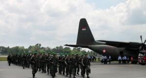 Personel Yonif 623 Wira Bhakti Utama TNI AD berjalan meninggalkan pesawat Hercules yang baru saja mengantarkan mereka tiba di Bandara Syamsudin Noor
