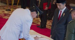 Presiden Joko Widodo (kedua kanan) menyaksikan Gubernur DKI Jakarta Basuki Tjahaja Purnama (kiri) menandatangani berita acara pelantikan di Istana Negara, Jakarta, Rabu (19/11).