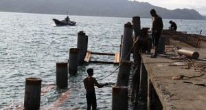 Pekerja memasang tiang pancang di pelabuhan kapal nelayan, Ulee Lheue, Banda Aceh, Minggu (16/11).