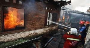 Petugas berusaha memadamkan rumah yang terbakar di Palinggam, Padang, Sumbar,
