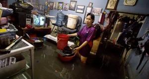 Warga merapihkan rumahnya dari banjir yang merendam permukiman di kawasan Kedoya, Jakarta, Sabtu (27/12).