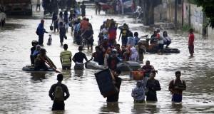 Sejumlah buruh pabrik dan warga menerobos banjir yang merendam kawasan industri di Jalan Mochammad Toha, Kabupaten Bandung, Jawa Barat, Senin (22/14).