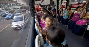 Anak-anak menggunakan bus Transjakarta gratis saat melintasi Jalan MH Thamrin, Jakarta, Kamis (18/12).