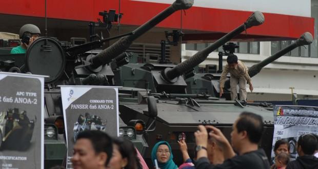 Warga saat berfoto dan menaiki kendaraan perang milik TNI yang dipamerkan di mal Tangerang City, Tangerang, Banten