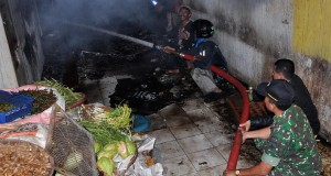 Petugas pemadam kebakaran dibantu anggota TNI dan warga berusaha memadamkan api saat terjadi kebakaran pasar Induk Wonosobo,  Jateng, Senin (22/12).