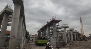 Warga melintas di area pengerjaan jalan Tol Sumo (Surabaya-Mojokerto) Seksi 1 dengan luas 58,76 hektar dan panjang 6,6 kilometer di Sepanjang, Sidoarjo, Jawa Timur, Senin (1/12).