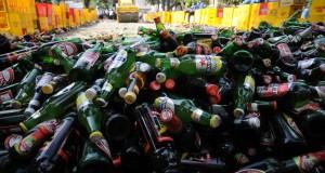 Petugas dibantu alat berat memusnahkan ribuan botol minuman keras dan oplosan di Balaikota Depok, Jawa Barat, Jum'at (19/12).