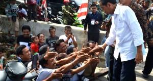Presiden RI, Joko Widodo berjabat tangan dengan warga yang telah lama menunggunya di Desa Sei Pancang Kecamatan Sebatik Utara di pintu masuk Pos TNI AL Pulau Sebatik Kabupaten Nunukan, Kalimantan Utara, Selasa (16/12).