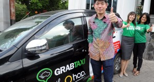Founder & Group CEO GrabTaxi Anthony Tan (kiri) bersama Head Marketing GrabTaxi Indonesia Kiki Rizki (kanan) dan Head Regional Launcher Adelene Foo, berfoto bersama di depan taxi, pada peluncuran program Perayaan Akhir Tahun, di Jakarta, Kamis (18/12).