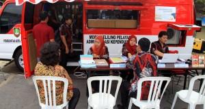 Petugas Dinas Kependudukan dan Catatan Sipil (Dispendukcapil) Kota Solo melayani warga yang mengurus surat-surat administrasi kependudukan usai peluncuran Mobil Keliling Pelayanan Administrasi Kependudukan di Jagalan, Solo, Jawa Tengah, Jumat (19/12).