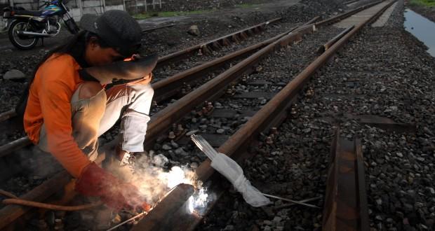 Seorang pekerja melakukan pengelasan jalur rel kereta api di Kawasan Stasiun Bangil, Pasuruan, Jatim, Rabu (17/12).