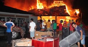 Sejumlah warga berusaha menyelamatkan barang Bupati Kabupaten Barito Utara, Kalimantan Tengah dari amukan api yang menghabiskan rumah jabatan bupati di Muara Teweh. Kamis (11/12) malam.