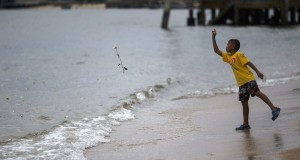 A boy throws a rose into the sea near a monument for victims of the 2004 tsunami in Ban Nam Khem