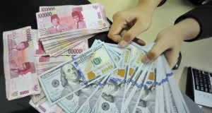 Petugas menghitung uang pecahan Dolar AS di layanan nasabah Bank BNI, Jakarta, Senin (26/1).