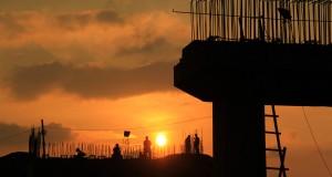 Pekerja bersiap meninggalkan lokasi pembangunan tiang penyangga jembatan jalan pantai saat terbvenam matahari di kawasan Pelabuhan Ulee Lheue, Banda Aceh, Rabu (28/1).