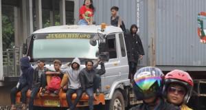 Sejumlah warga mengabaikan keselamatannya dengan duduk di bagian depan dan atas truk kontener yang melintas di Jalan Daan Mogot, Cengkareng, Jakarta Barat, Senin (26/1)
