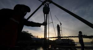 Dua pekerja tengah memasang lantai beton dermaga yang masih dalam proses pembangunan di Pelabuhan wisata Kalimas, Manado, Sulawesi Utara, Senin (26/1).