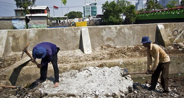 Pekerja menyelesaikan perbaikan tanggul Kali Sunter di Jalan Yos Sudarso, Jakarta, Rabu (28/1).