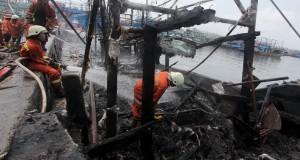 Petugas pemadam kebakaran mencoba memadamkan api yang membakar kapal milik nelayan yang terbakar di Pelabuhan Muara Angke, Jakarta, Jumat (27/2).