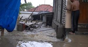 Warga melihat bangunan rumah yang ambruk akibat diseret  banjir, di Jalan Jokotole, Pamekasan