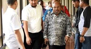 Gubenur Papua Lukas Enembe (kedua kanan) berjalan sebelum menghadiri pertemuan mengenai kesepakatan pembangunan smelter di Timika, Papua, Minggu (15/2)