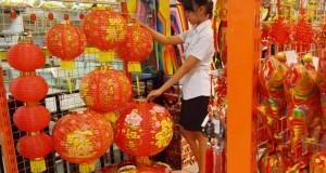Pramuniaga menata pernak-pernik Imlek di sebuah pusat perbelanjaan di Kota Madiun, Jatim, Rabu (28/1).