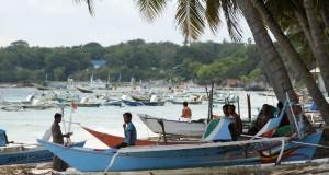 Nelayan berada di samping perahu yang ditambatkan di perkampungan nelayan Situbaru, Bulukumba, Sulawesi Selatan, Minggu (22/2).