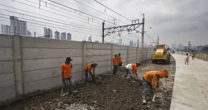 Sejumlah pekerja menyelesaikan proyek pembangunan jalan inspeksi pada sepanjang aliran banjir kanal barat di Jakarta, Selasa (3/3).