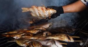 Seorang pekerja mengasapi ikan di sebuah industri ikan asap rumahan di Surabaya, Jawa Timur, Minggu (15/3