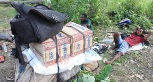 Pengendara ojek pengantar kebutuhan pokok dari Marauke, Papua ke Papua Nugini beristirahat di perbatasan Indonesia-Papua Nugini di Distrik Sota, Merauke, Papua,