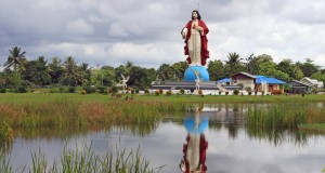 Warga melintas dekat Patung Hati Kudus Yesus di Merauke, Papua, Sabtu (21/3)