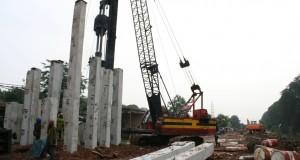 Pekerja menggunakan alat berat melakukan pemasangan tiang pancang proyek jalan Tol Bekasi - Cawang - Kampung Melayu (Becakayu) di Kelurahan