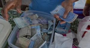 Seorang pedagang menghitung uang rupiah dan ringgit Malaysia hasil penjualan berbagai jenis kebutuhan sehari-hari di Pasar Sei Pancang, Kecamatan Sebatik Utara, Nunukan, Kaltara, Minggu (29/3)