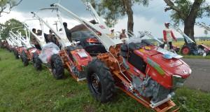 Sejumlah warga melintas di dekat deretan traktor yang akan dibagikan ke petani saat kunjungan kerja Presiden Joko Widodo di Desa Jetis, Kec. Jetis, Ponorogo, Jatim, Jumat (6/3)