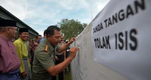 Danrem 042/Gapu Jambi Kolonel Inf Harianto (kanan) didampingi sejumlah tokoh membubuhkan tanda tangan menolak paham ISIS usai Deklarasi Penolakan Paham ISIS di lapangan Korem 042/Gapu, Jambi.